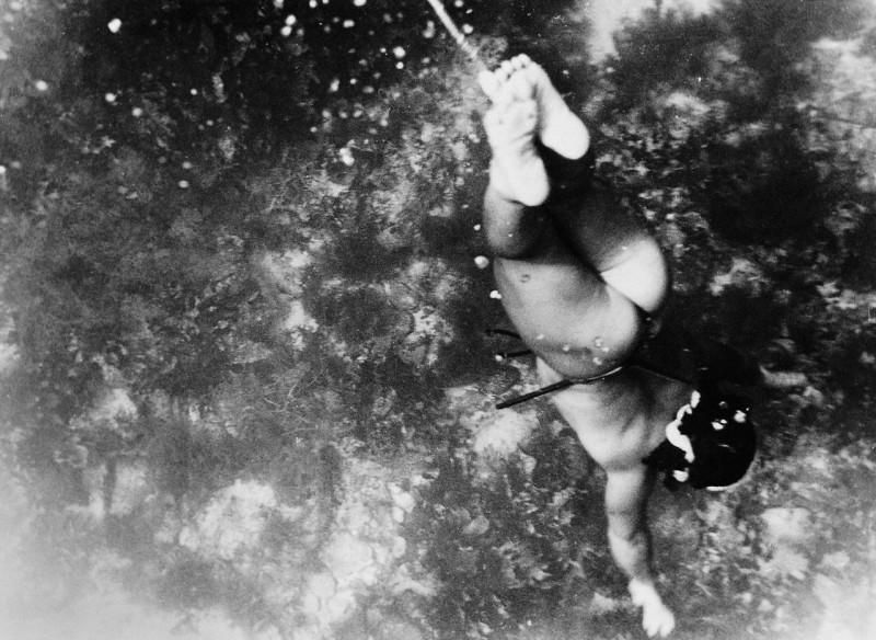 Una ama se sumerge sujetando la cuerda entre sus piernas (Fosco Mariani).